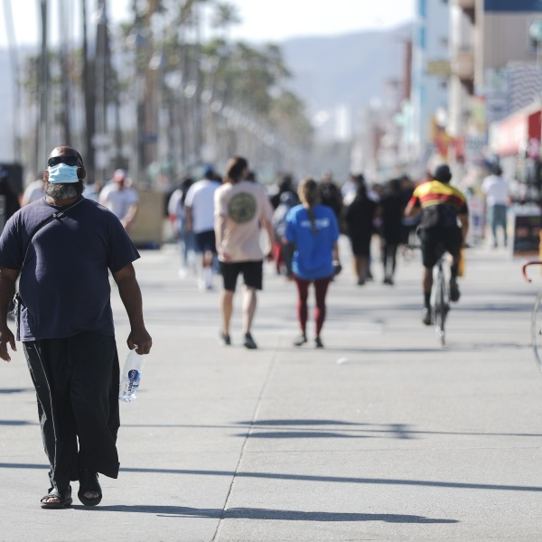 A man wears a face mask as he walks along the Venice Beach boardwalk on the day Los Angeles County reopened its beaches, which had been closed due the coronavirus pandemic, on May 13, 2020, in Venice, California. (Mario Tama/Getty Images)