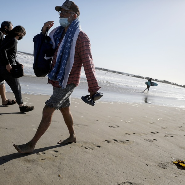 People wear face masks walking along Venice Beach on the day L.A. County reopened its beaches, which had been closed due to the coronavirus pandemic, on May 13, 2020 in Venice. (Mario Tama/Getty Images)