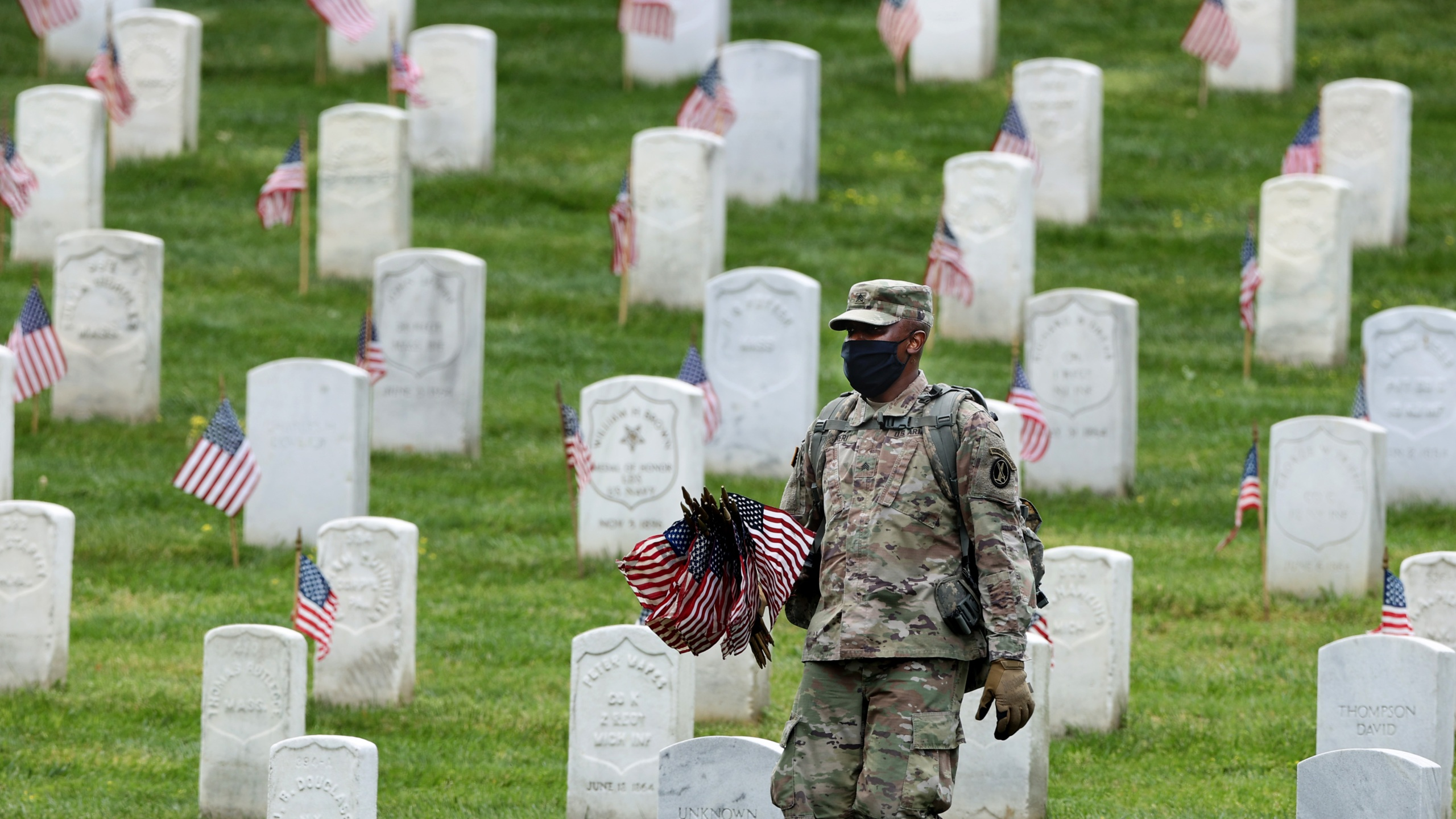 "Wearing face masks to reduce the risk of spreading the novel coronavirus, a soldier from the 3rd Infantry Regiment, or the ""Old Guard,"" works to place U.S. flags in front of every grave site ahead of the Memorial Day weekend in Arlington National Cemetery on May 21, 2020 in Arlington, Virginia. (Chip Somodevilla/Getty Images)"