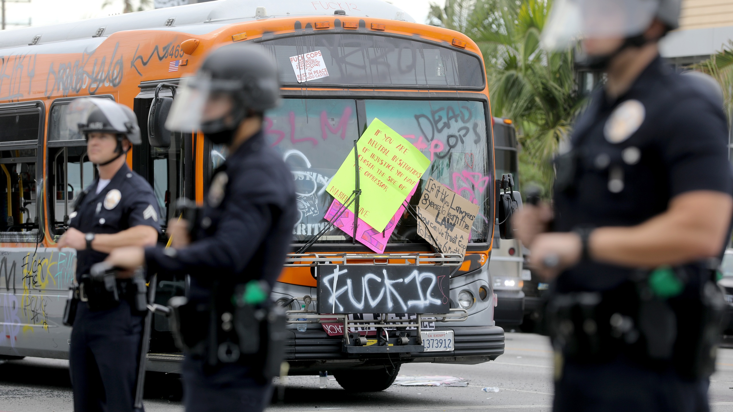 Police officers keep watch near a damaged bus during demonstrations following the death of George Floyd on May 30, 2020, in Los Angeles. (Mario Tama/Getty Images)