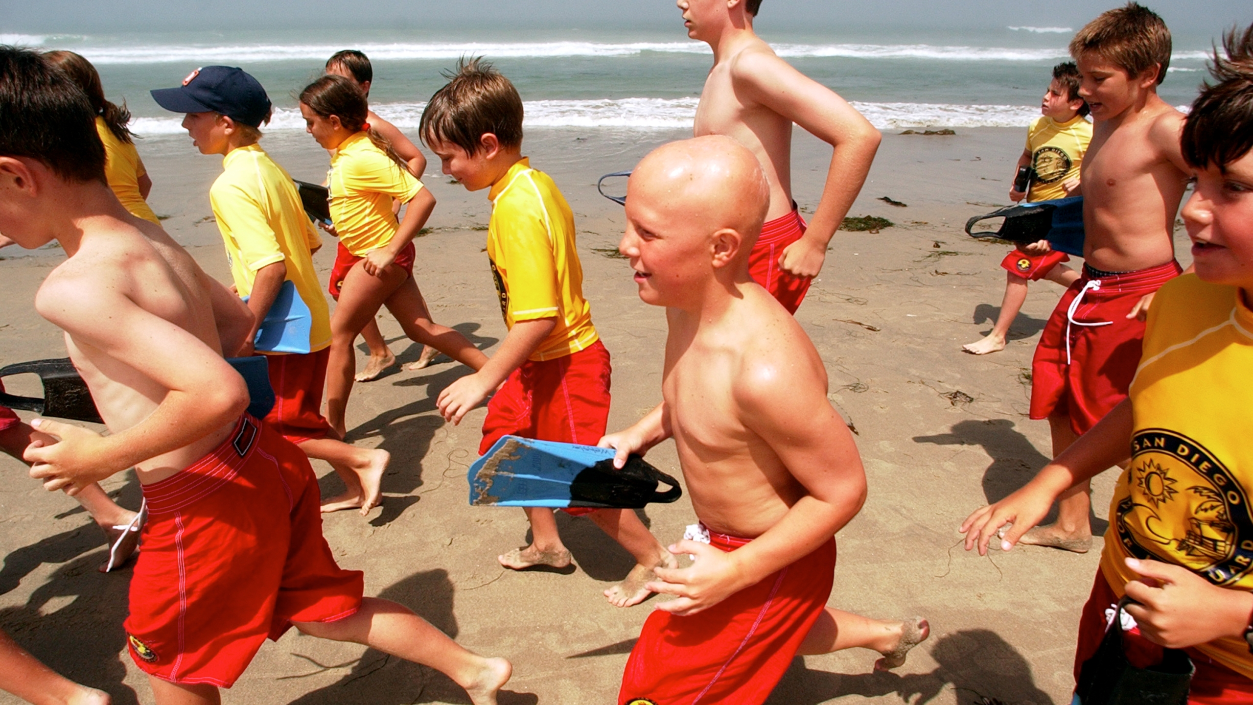 A group of junior lifeguards enjoy a run on the beach on July 3, 2003, at Pacific Beach in San Diego, California. (Sandy Huffaker/Getty Images)