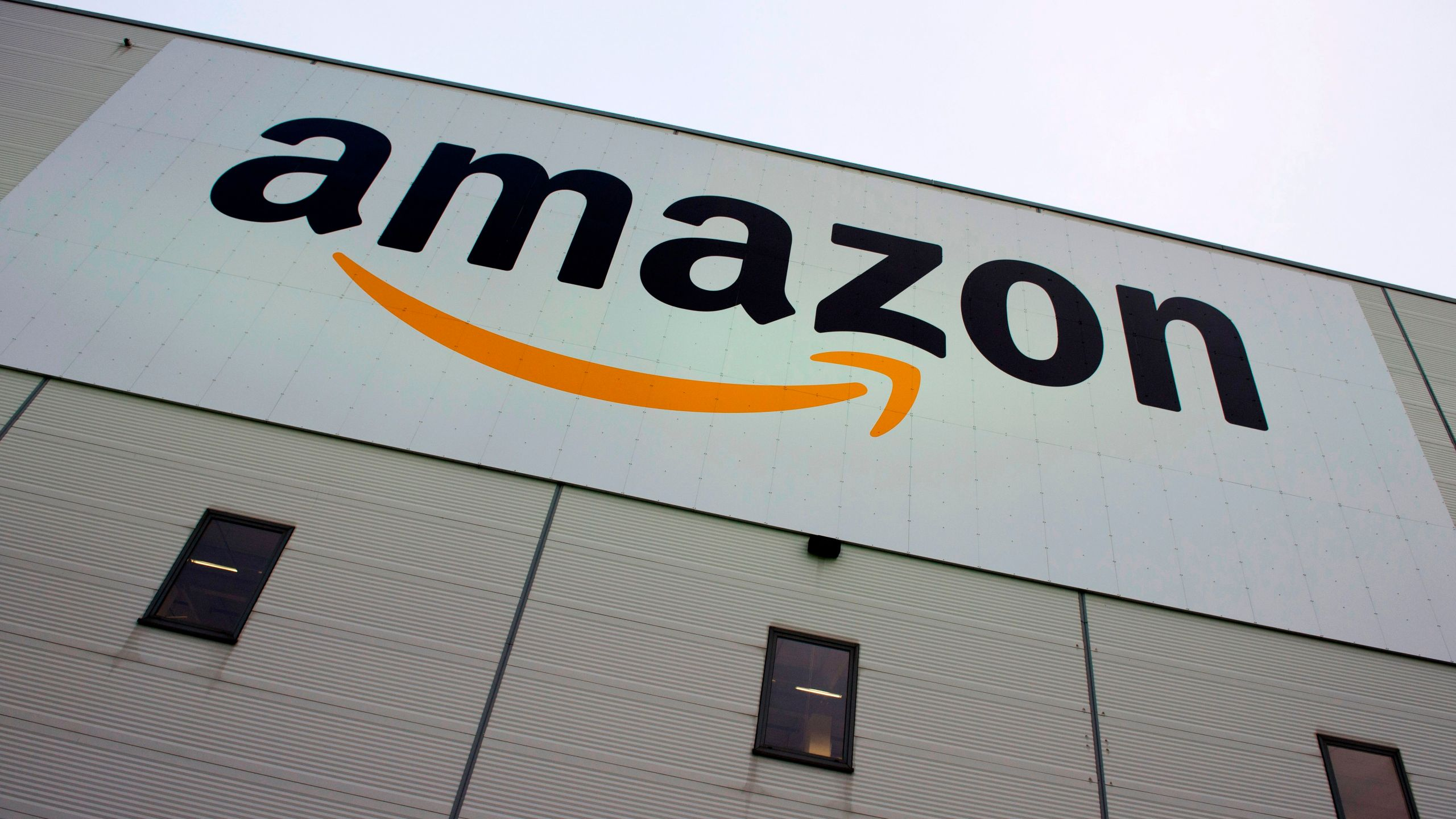 The logo of online retail giant Amazon is displayed on the Brieselang logistics center, west of Berlin on November 11, 2014. (JOHN MACDOUGALL/AFP via Getty Images)