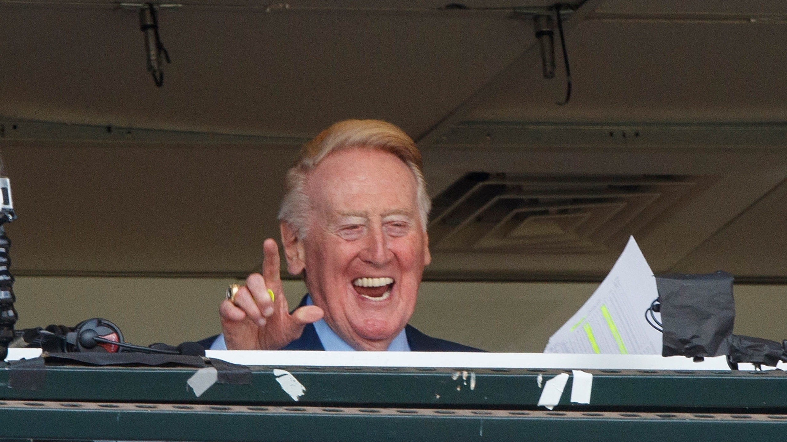 Vin Scully waves to fans in the broadcast booth before the game between the San Francisco Giants and the Los Angeles Dodgers at AT&T Park on October 2, 2016, in San Francisco. (Jason O. Watson/Getty Images)