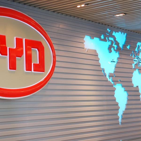 The BYD Auto (Build Your Dreams) logo looms over a scale model of the company's factory in Shenzhen on July 27, 2009. (LAURENT FIEVET/AFP via Getty Images)