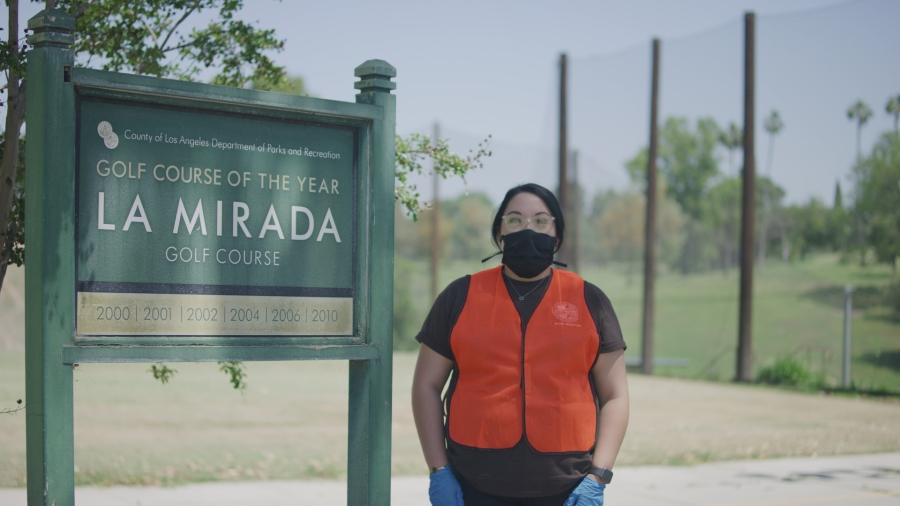 A park monitor for Los Angeles County Parks and Recreation stands beside the sign for La Mirada Golf Course in a photo provided by the agency on May 10, 2020.