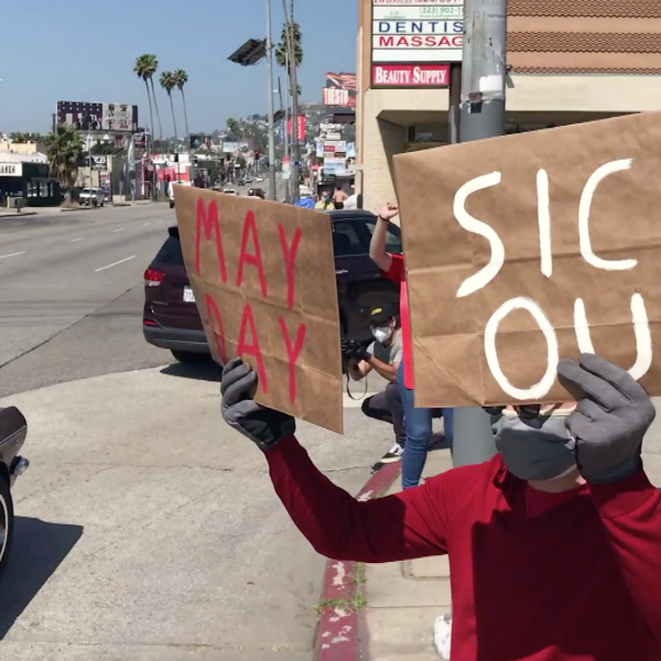 """Protestors holds signs that read """"May Day"""" and """"Sick out"""" outside a Ralphs store in Hollywood on May 1, 2020. (KTLA)"""