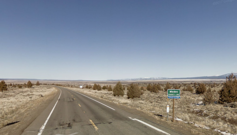 A sign showing southern boundary of Modoc County on U.S. 395 is shown in a Google Maps Street View image.