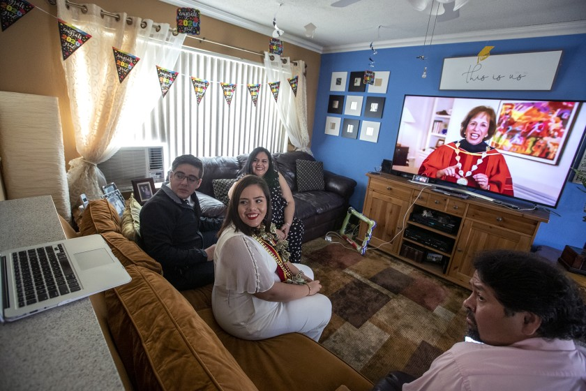 Maria Morales, center, a member of the USC Class of 2020, attends her virtual graduation via Zoom with her brother Manny Morales, left, mother Pilar Morales and stepdad Victor Ramos, right, in Orange.(Brian van der Brug / Los Angeles Times)