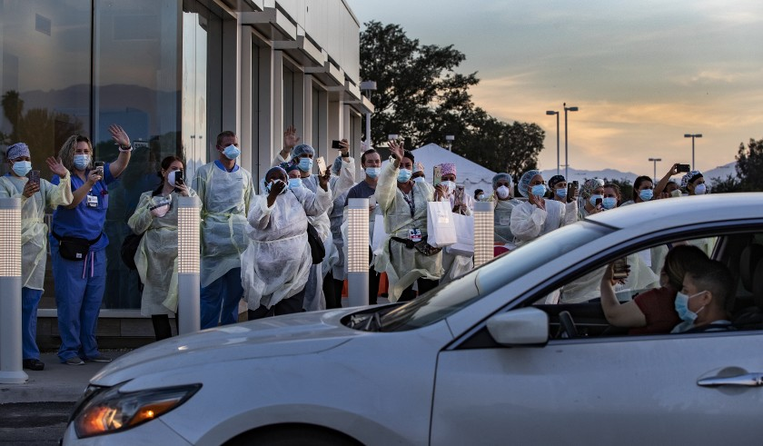 Doctors and nurses wave thanks as residents pay tribute to them during a drive-by rally honoring frontline heroes at Riverside University Health System in Moreno Valley.(Gina Ferazzi / Los Angeles Times)