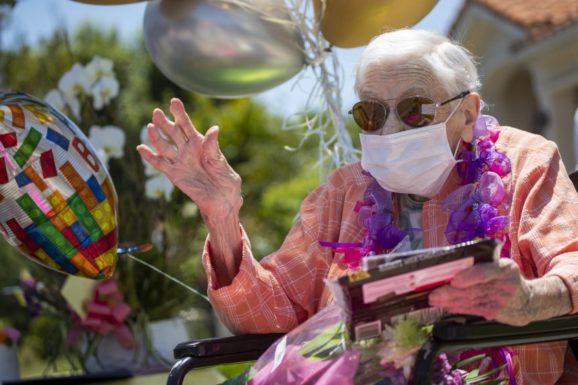 Mildred Stratton waves to a caravan of cars led by the Alhambra police and fire departments parading past her home, celebrating her 102nd birthday on May 20 in Alhambra.(Allen J. Schaben / Los Angeles Times)