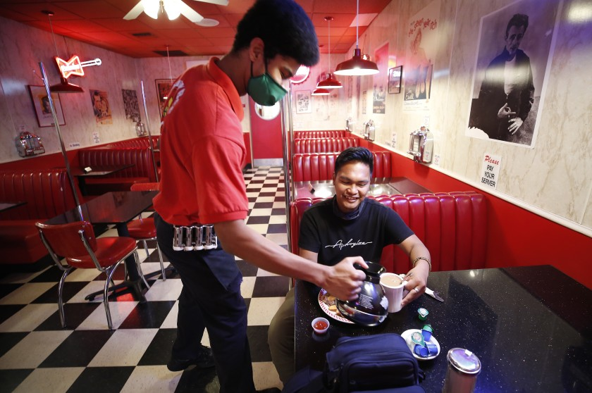 At the Busy Bee Cafe along Main Street in downtown Ventura, Bryson Finger serves coffee to Jeric Gambon, 24, as he enjoys breakfast May 21, 2020.(Al Seib / Los Angeles Times)