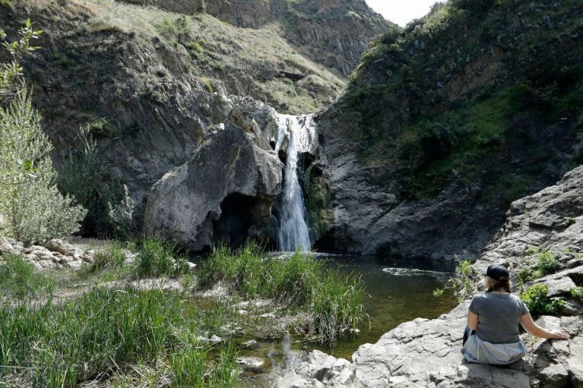 A woman enjoys the view of Paradise Falls at Wildwood Regional Park in Thousand Oaks in this 2019 file photo. The area is now closed to visitors.(Myung J. Chun / Los Angeles Times)