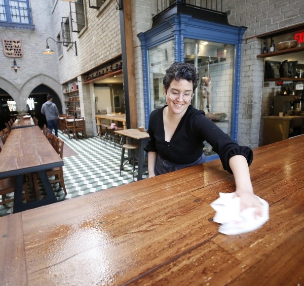 Grace Curran, restaurant manager of Republique, wipes tabletops with disinfectant. L.A. County has received permission from the state to resume in-person dining.(Al Seib / Los Angeles Times)