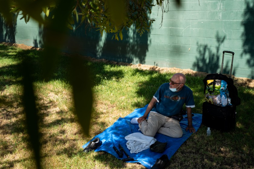 Terrance Whitten rests in the shade at Pan Pacific Park on May 1, 2020, in Los Angeles. The 67-year-old has been waiting in the queue for nine days to get into a hotel room. (Kent Nishimura / Los Angeles Times)