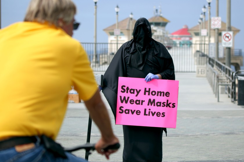 The Grim Reaper, also known as Spencer Kelly, holds a sign at Pier Plaza in Huntington Beach on Friday. The Huntington Beach resident was part of a three-person protest organized by Indivisible OC 48.(Raul Roa / Times Community News)