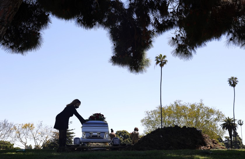 Clarice Kavanaugh places a hand on the casket of her friend Charles Jackson at Inglewood Park Cemetery on April 15, 2020. Jackson was diagnosed with COVID-19 after returning home from a ski trip in Idaho and died days later in the hospital. (Christina House / Los Angeles Times)