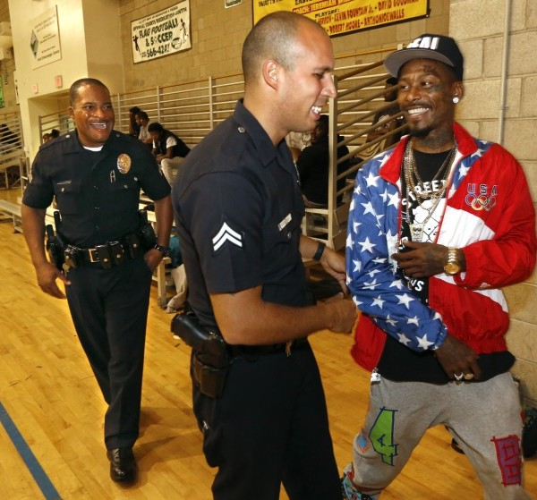 Eric Romero, right, a resident at the Imperial Courts Housing Development in Watts, chats with Los Angeles police officers Delano Hutchins, left, and Angelo Marzan in 2015. (Mel Melcon / Los Angeles Times)