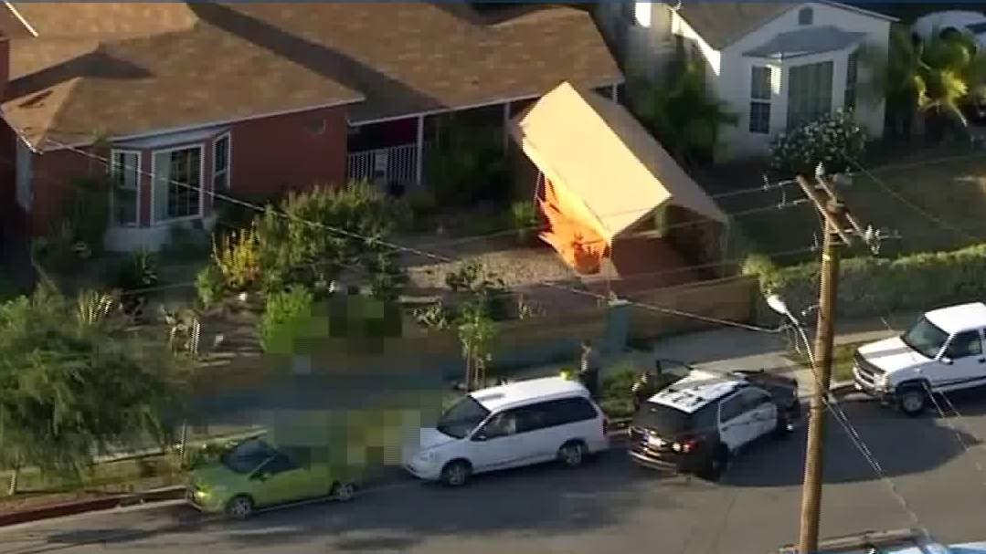 A dead body lies on the sidewalk after deputies shot and killed a man in Westmont on May 26, 2020. (KTLA)