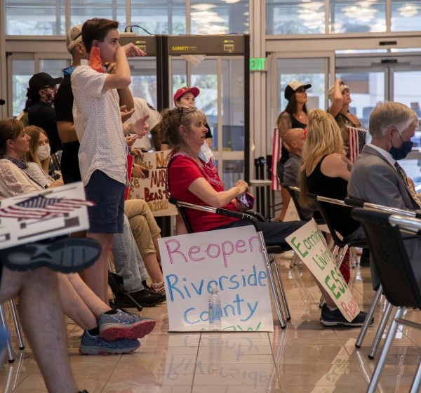 Residents who want public health orders rescinded crowd together in the lobby to watch video monitors of an emergency Riverside County Board of Supervisors meeting at the County Administrative Center on May 8, 2020. (Gina Ferazzi / Los Angeles Times)