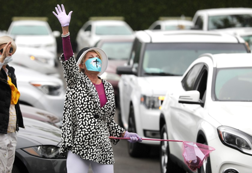 MaryAnn Lawson collects prayer requests from people gathering in their cars in a Santa Ana parking lot before an Easter service with the Rev. Robert A. Schuller on April 12, 2020. (Christina House / Los Angeles Times)