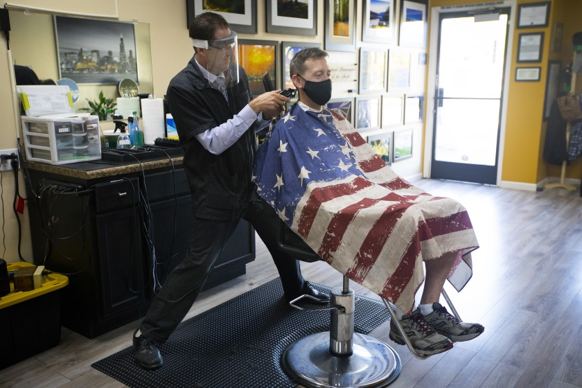 Dan Collins, co-owner of Skyline Barbershop in Temecula, cuts Gene Kelley's hair on May 26, 2020, the first day they could open. (Francine Orr / Los Angeles Times)