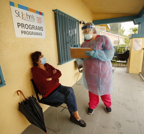 Maria Banderas, left, answers questions from medical assistant Dolores Becerra before being tested for the coronavirus at St. John's Well Child and Family Center in South Los Angeles. (Al Seib / Los Angeles Times)
