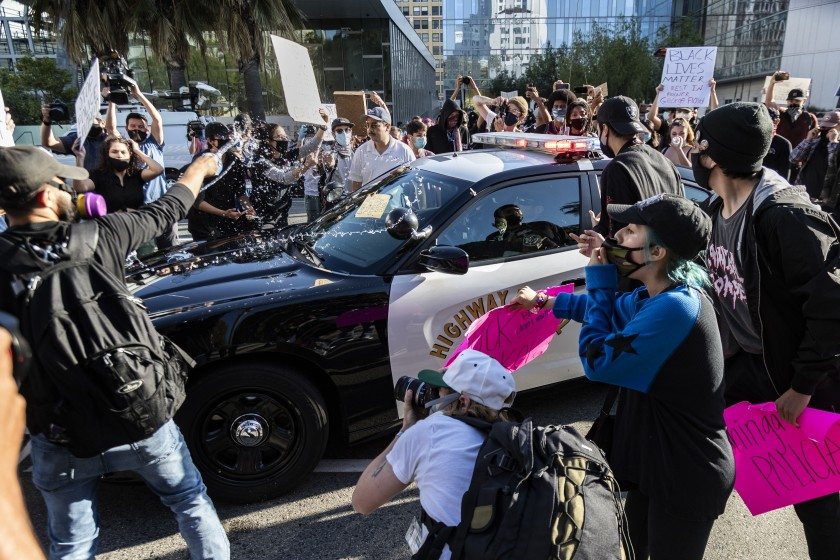 Black Lives Matter protesters swarm a California Highway Patrol vehicle in front of Los Angeles police headquarters on May 28, 2020. (Gina Ferazzi / Los Angeles Times)