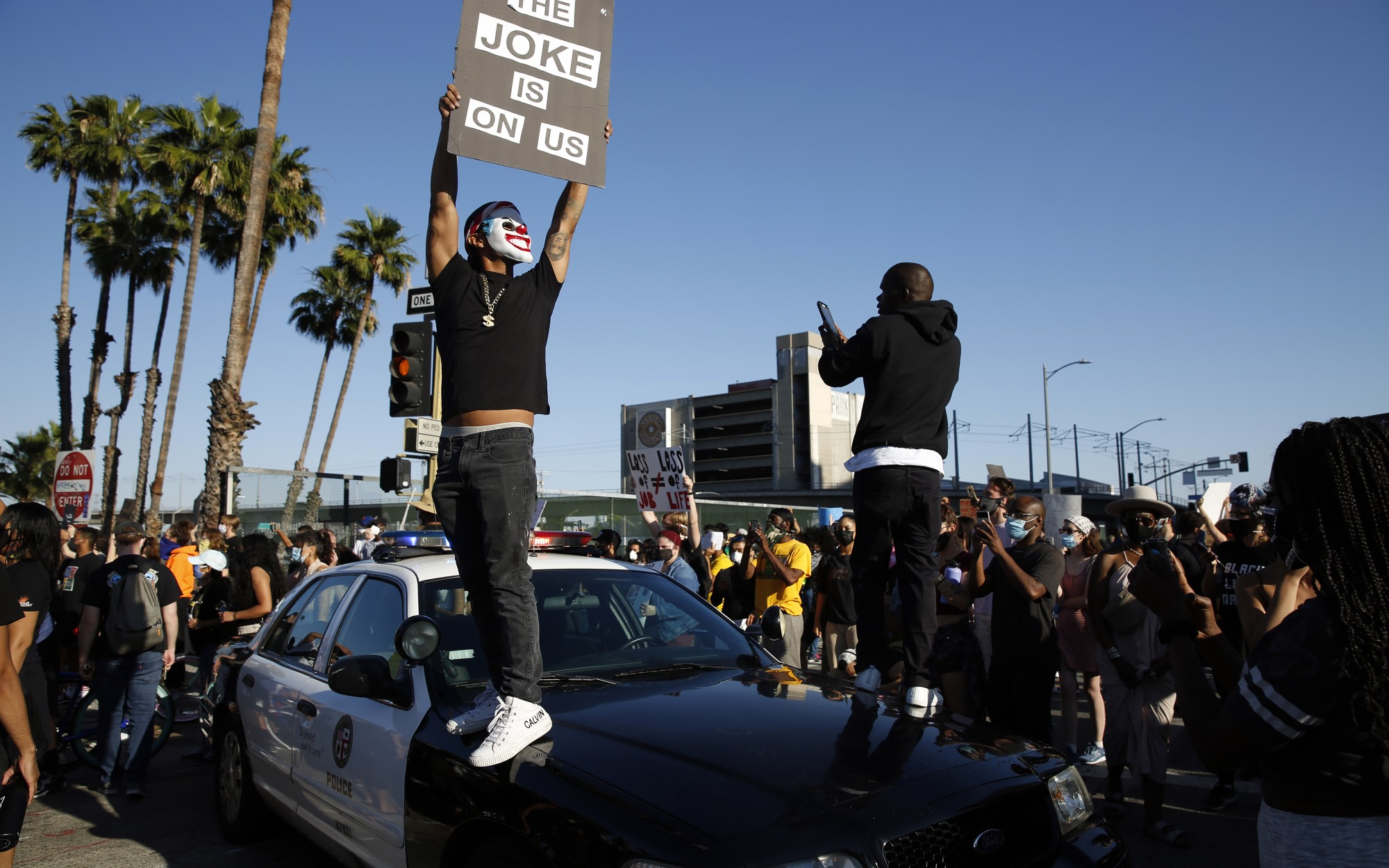 Protesters stand on a Los Angeles police cruiser on May 27, 2020, during a downtown L.A. protest over the death of George Floyd in Minneapolis police custody. (Dania Maxwell / Los Angeles Times)