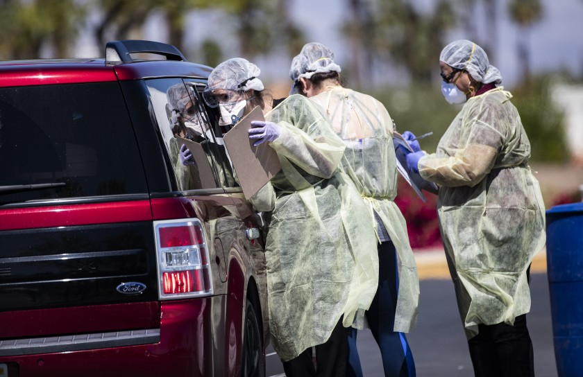 Riverside County medical personnel screen a carload of people at a coronavirus drive-though testing facility on March 24, 2020. (Gina Ferazzi / Los Angeles Times)
