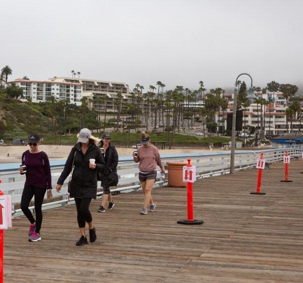 A group of women walk the San Clemente Pier on May 18, 2020. (Gabriella Angotti-Jones / Los Angeles Times)