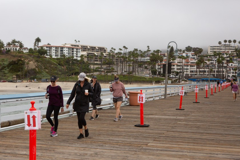 A group of women walk the San Clemente Pier on May 18, 2020. (Gabriella Angotti-Jones / Los Angeles Times)