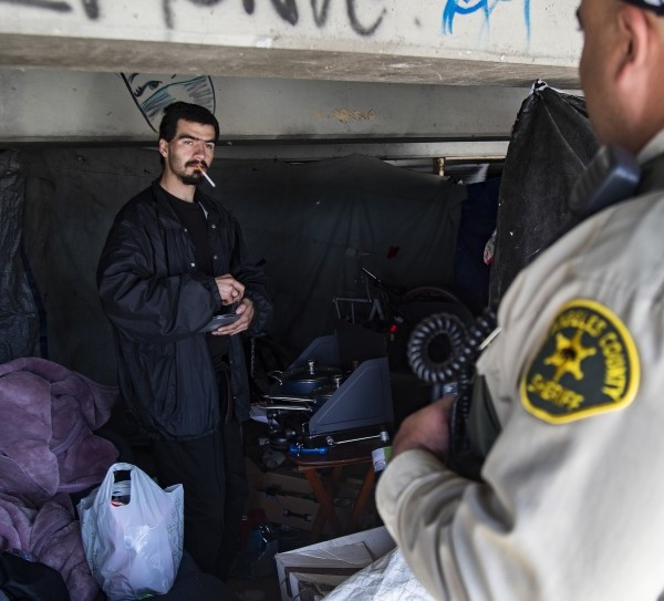 L.A. County sheriff's Deputy Michael Tadrous of the Homeless Outreach Services Team talks with Shawn Troncozo, 24, about how to prevent the spread of the coronavirus near the San Gabriel River in this undated photo. (Credit: Gina Ferazzi / Los Angeles Times)