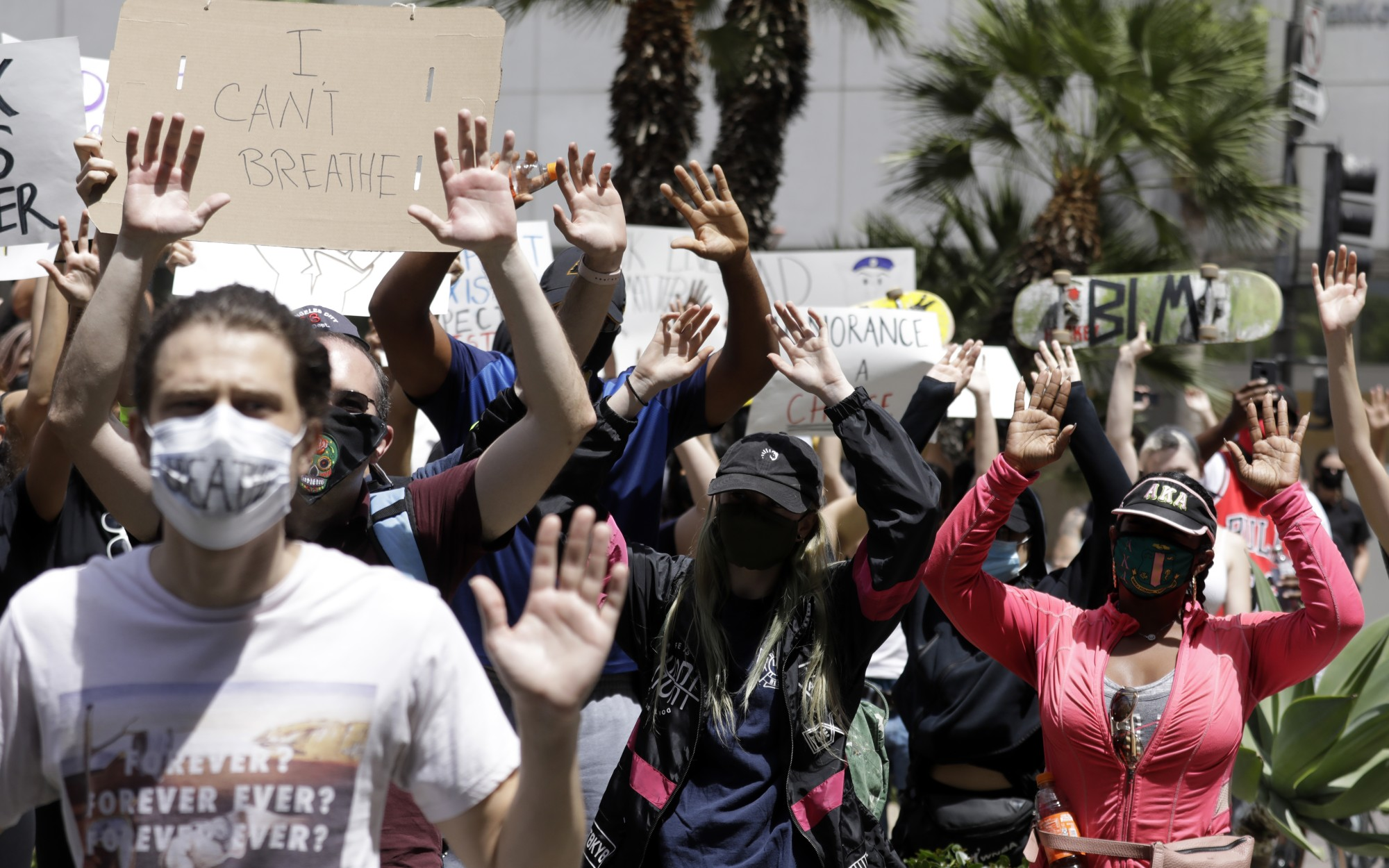 "Protesters raise their arms while chanting, ""Hands up, don't shoot!"" at Pershing Square in downtown Los Angeles on May 31, 2020. (Myung J. Chun / Los Angeles Times)"