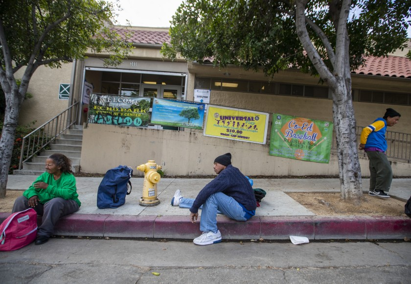 Tyrone Dixon, 53, center, waits with fellow homeless people outside the Echo Park Community Center, one of several Los Angeles recreation centers that have been converted to shelters during the COVID-19 pandemic. (Allen J. Schaben / Los Angeles Times)