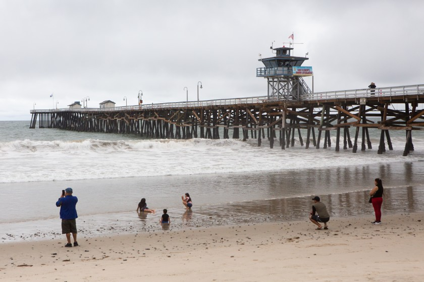 Families practice social distancing while playing in the water and sand near the San Clemente Pier on May 18.(Gabriella Angotti-Jones / Los Angeles Times)
