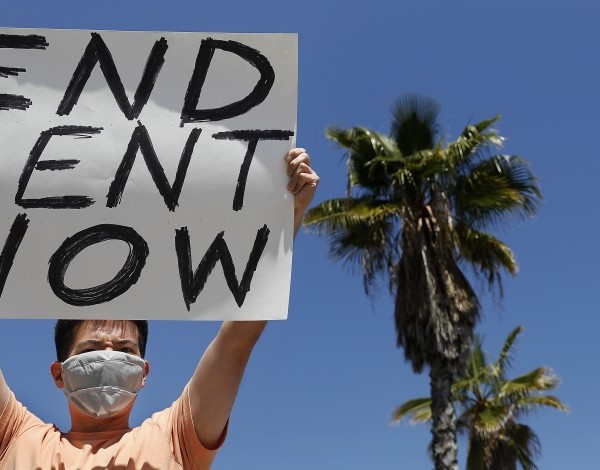 A protester demands rent forgiveness for the month of April due to the coronavirus pandemic's economic fallout. (Los Angeles Times)