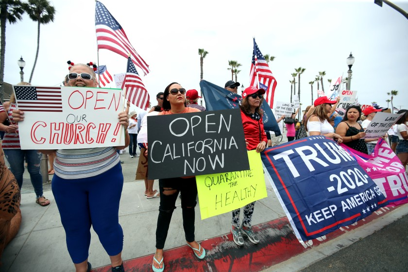 Protesters call for opening churches and lifting remaining virus restrictions in California during a protest Saturday in Huntington Beach.(Raul Roa / Los Angeles Times)