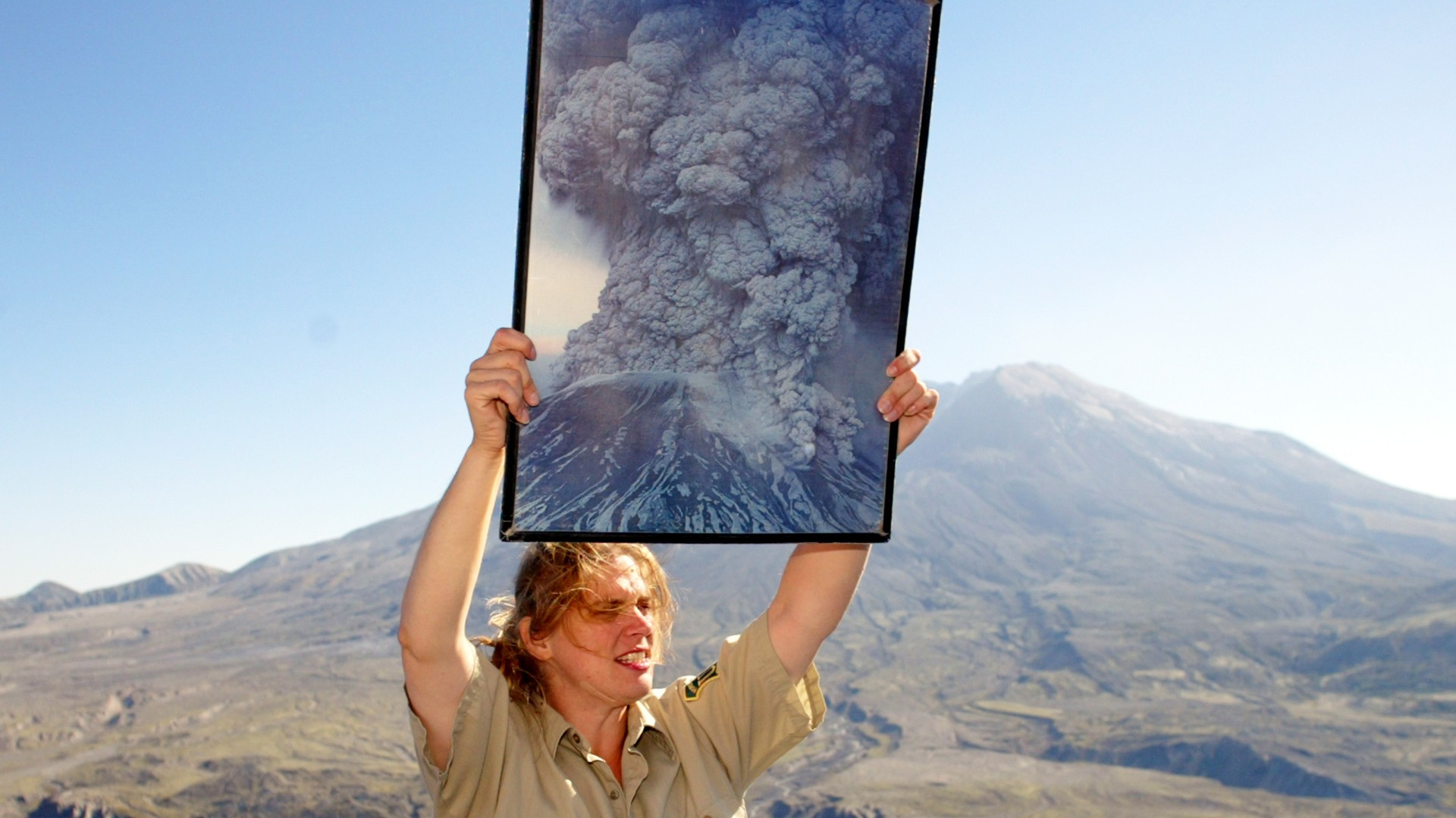 Forest service employee Anna White holds up a photo of the original eruption in 1980 while talking to visitors at Mount St. Helens from the Johnston Ridge Observatory on October 1, 2004 (Mitchelldyer/Getty Images)