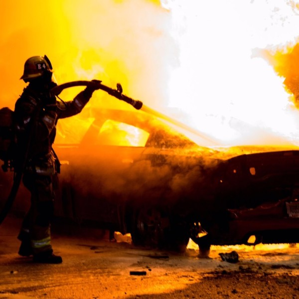 A firefighter works to put out a car fire in Anaheim on May 29, 2020. (Anaheim Police Department)