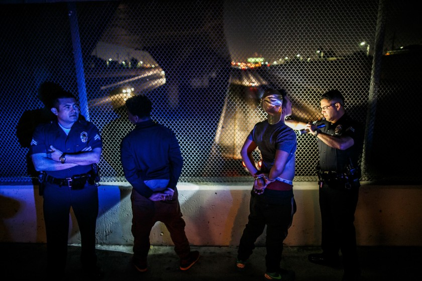 Officers from the LAPD's Metropolitan Division check a driver and passenger for tattoos while other officers search their vehicle in November 2015. (Marcus Yam / Los Angeles Times)