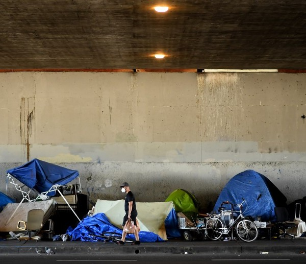 A man walks by a homeless encampment on Venice Boulevard under the 405 Freeway. A federal judge has ordered the city and county of Los Angeles to relocate thousands of homeless people living near freeways starting on Friday. (Wally Skalij/Los Angeles Times)