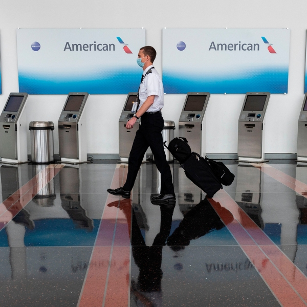 An airline employee walks past empty American Airlines check-in terminals at Ronald Reagan Washington National Airport in Arlington, Virginia, on May 12, 2020. (ANDREW CABALLERO-REYNOLDS/AFP via Getty Images)