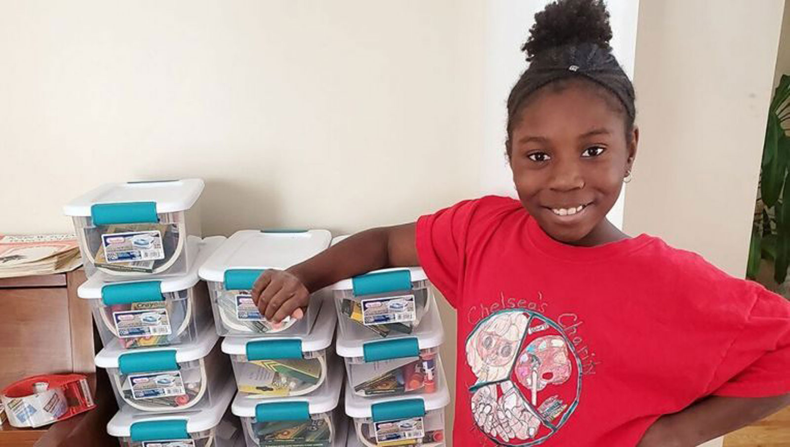 Chelsea Phaire, founder of Chelsea's Charity, poses with art kits she made for children in this photo provided by Candace Phaire to CNN in May 2020.