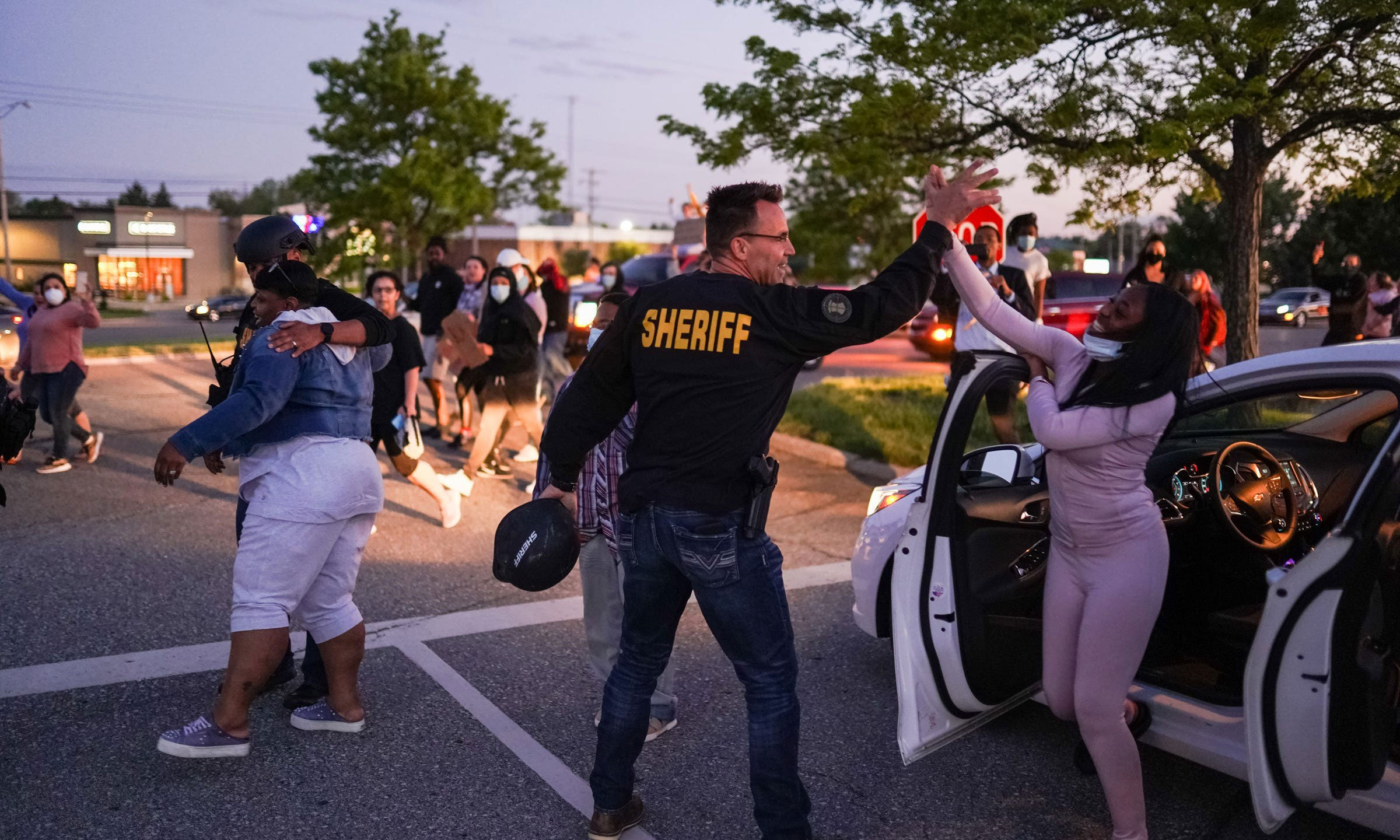 Genesee County Sheriff Chris Swanson high-fives a woman who called his name as he marches with protestors of police brutality and in memory of George Floyd on May 30, 2020, in Flint Township, Michigan. (Ryan Garza/USA Today Network via Reuters)