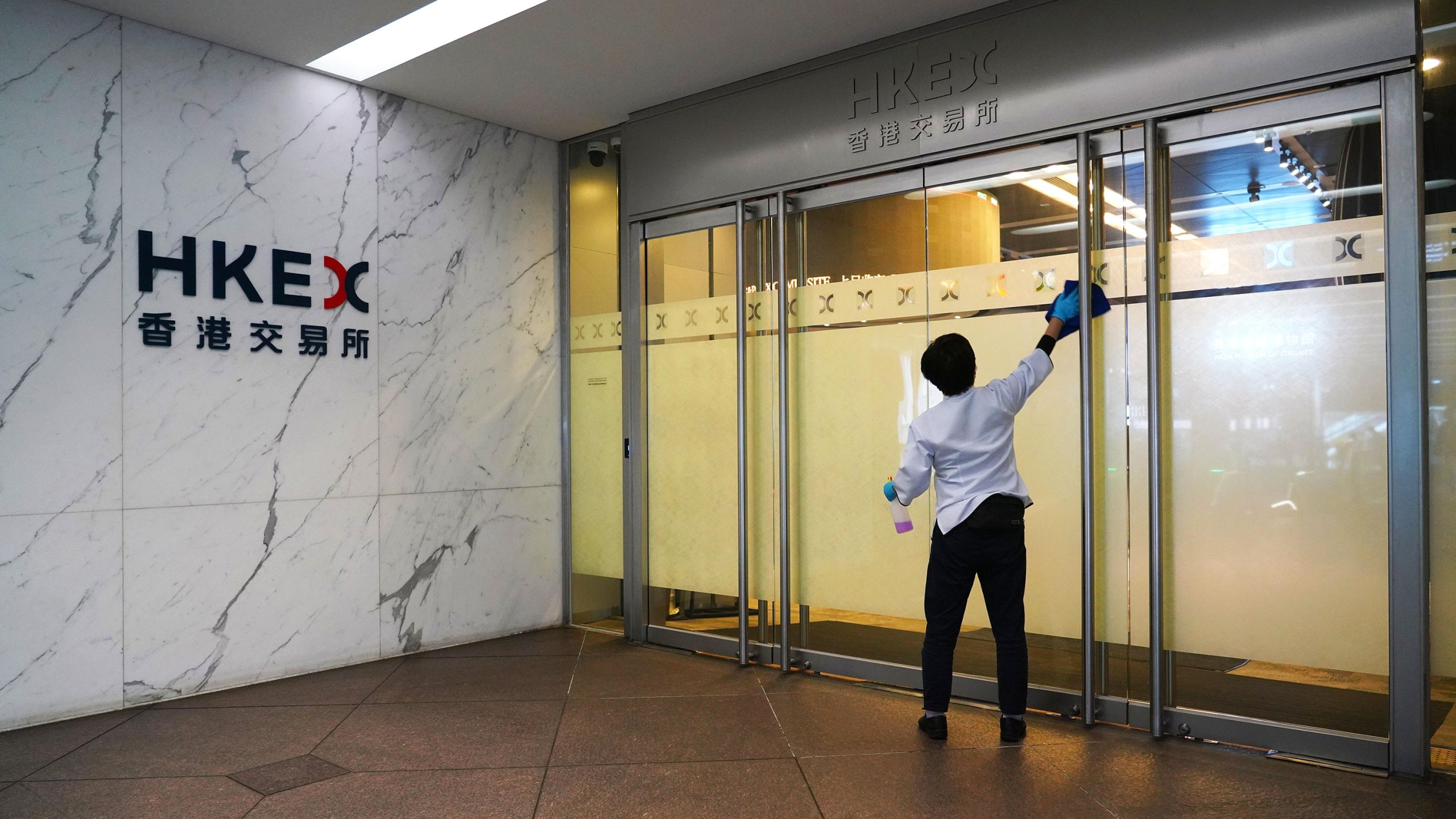 A cleaner disinfects a door of HKEX (Hong Kong Stock Exchange) Connect Hall on March 27, 2020 in Hong Kong, China. (Zhang Wei/China News Service via Getty Images)