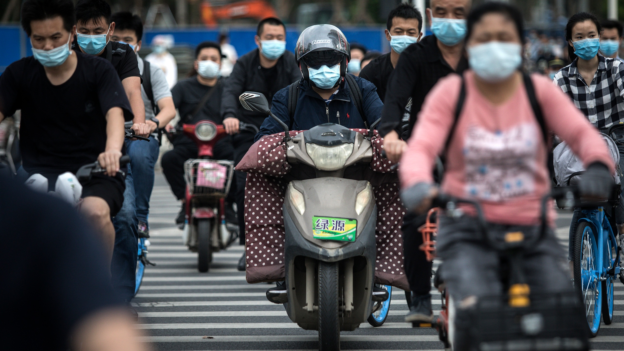 Residents wears face masks while riding their bicycles on May 11, 2020 in Wuhan, China. (Getty Images)