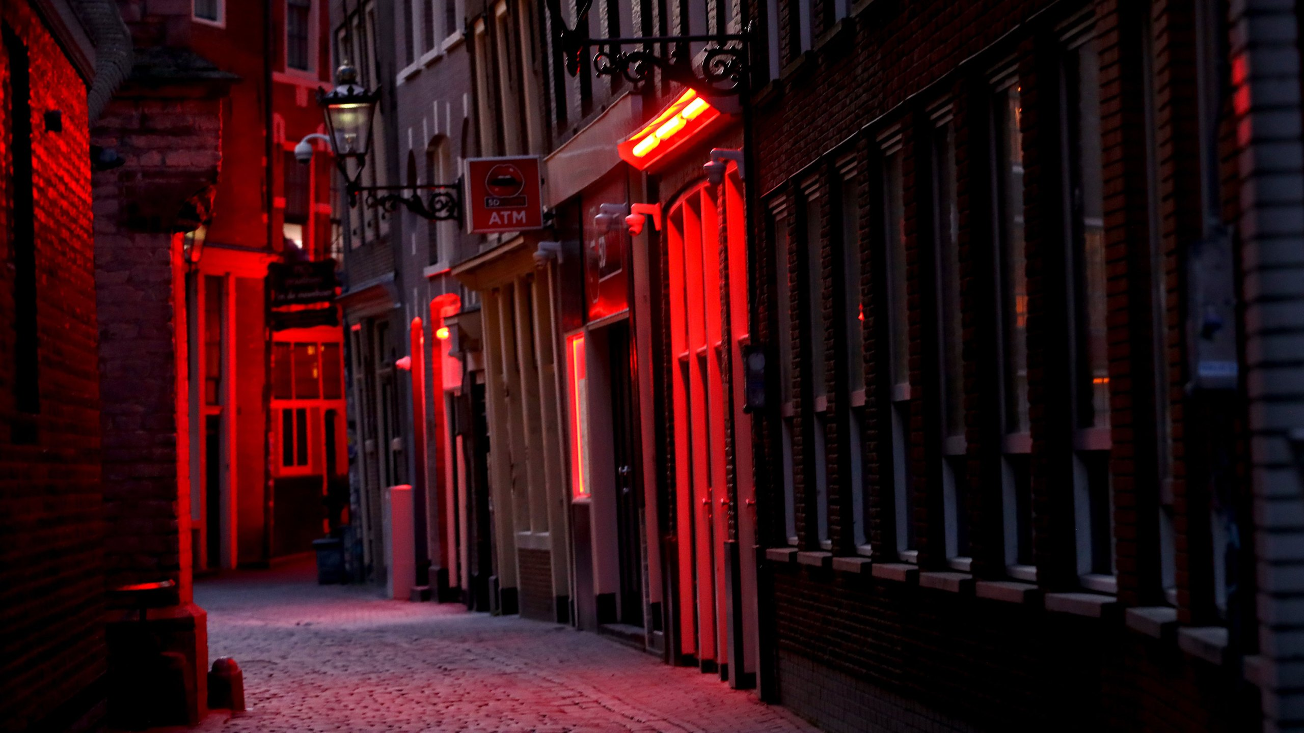 "A general view of the 'Windows' in the ""Red Light District"" which comes from the red neon lights that highlight the windows where prostitution is legal, but the area is also famous for its canals, coffeeshops selling marijuana or cannabis, brothels, sex shops and museums on what would be a usually busy Saturday night on April 4, 2020 in Amsterdam, Netherlands. (Dean Mouhtaropoulos/Getty Images)"
