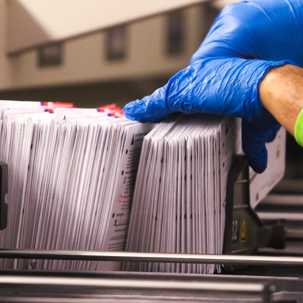 An election worker handles vote-by-mail ballots coming out of a sorting machine for the presidential primary at King County Elections in Renton, Washington on March 10, 2020. (JASON REDMOND/AFP via Getty Images)