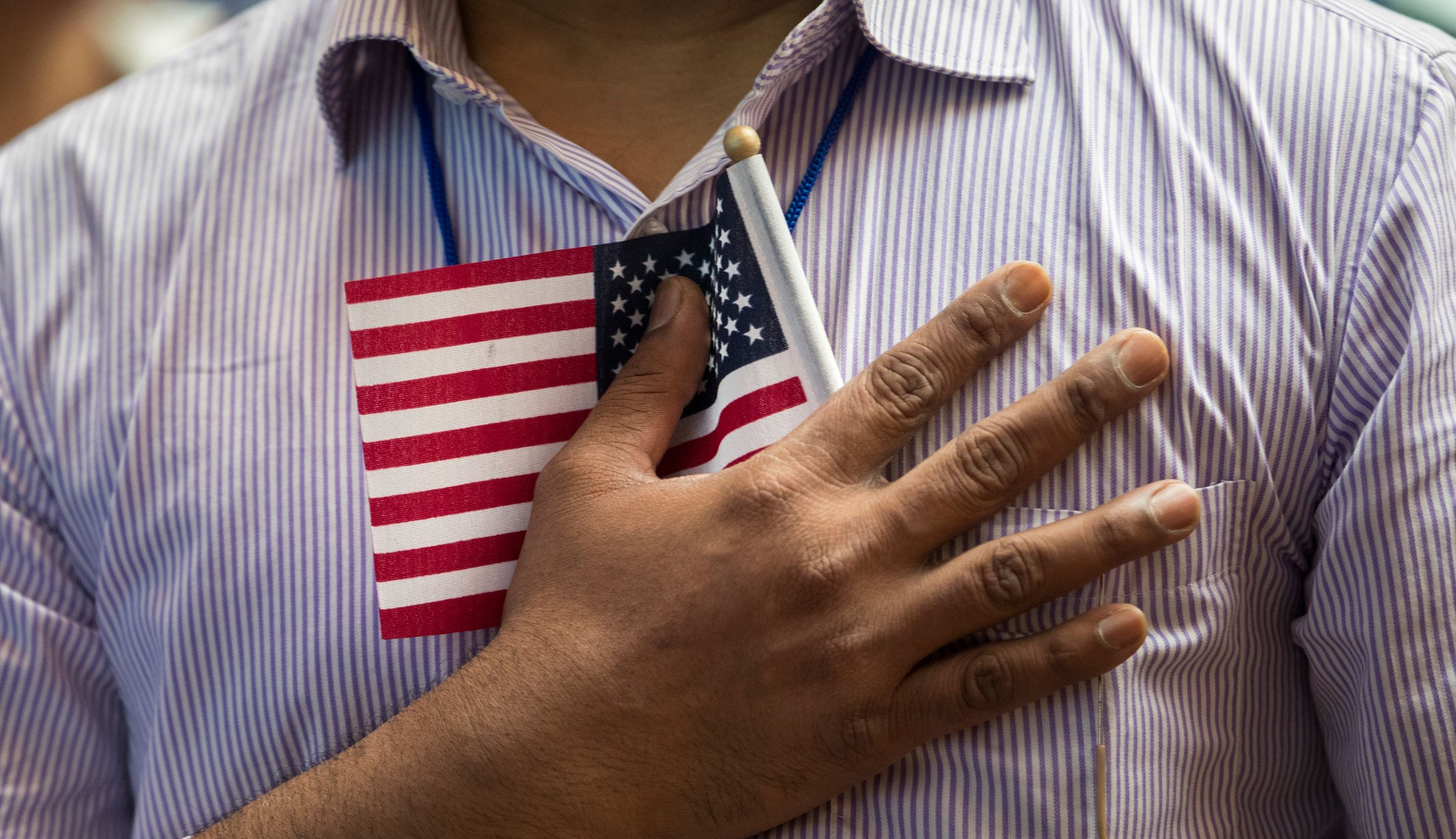 A new U.S. citizen holds a flag to his chest during the Pledge of Allegiance during a naturalization ceremony at the New York Public Library, July 3, 2018 in New York City. (Drew Angerer/Getty Images)