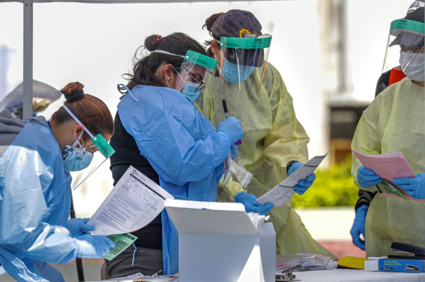 San Bernardino County Department of Public Health workers collect coronavirus samples at a drive-through testing site in Montclair in this undated photo. (Irfan Khan / Los Angeles Times)